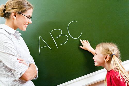 Девочка у доски пишет Английские буквы