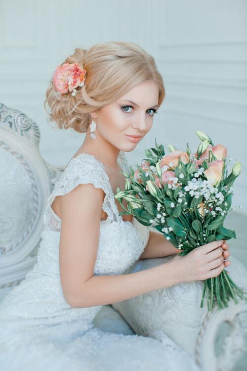 Красивая невеста с цветами руках и в укладке волос