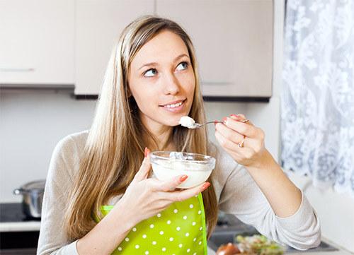Красивая девушка ест творог