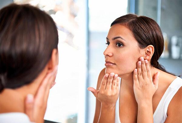 женщина проверяет не шелушиться ли кожа лица