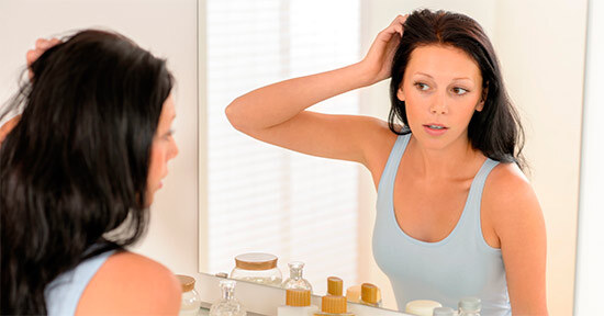 Женщина смотрит на состояние своих волос в зеркале