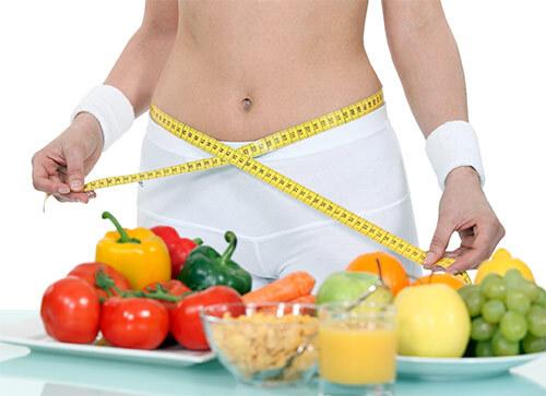 Оголенный женский торс, измерение гибким метром талии, овощи
