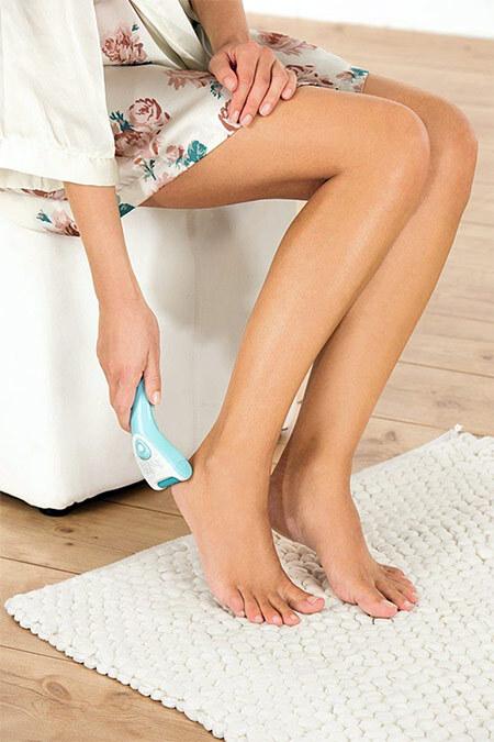 Женщина пользуется электрической пилкой для ног